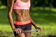 Attractive fitness young woman showiong her perfect abs. Health concept. Fit woman holding rubber band. royalty free stock images