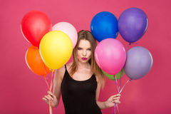 Attractive flirty woman with colorful balloons planning surprise Royalty Free Stock Image