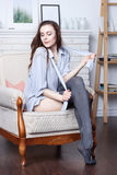 An attractive flirty young brunette is lying in a large soft chair Royalty Free Stock Images