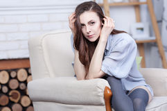 An attractive flirty young brunette is sitting in a large soft chair Royalty Free Stock Photos