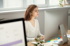 Attractive focused female employee working on desktop in coworki. Attractive focused female employee intern working on desktop sitting at coworking space shared royalty free stock image