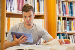 Attractive focused student using tablet and turning page Royalty Free Stock Images