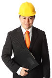 Attractive foreman in hardhat. Attractive foreman wearing a suit and tie with a yellow helmet, holding a clipboard. White background royalty free stock photo