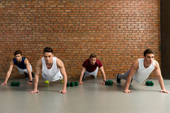 Attractive four men training body. Handsome young sportsmen doing push-ups in gym. They are looking forward with confidence Stock Photos