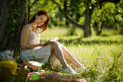 Attractive foxy woman reading book sitting in garden with her back close to tree. Summer garden, girl sitting on grass, enjoying nature. Attractive foxy woman Stock Images