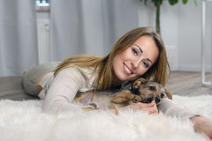 Attractive friendly woman cuddling with her dog Royalty Free Stock Image