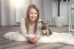 Attractive friendly woman with her dog. Attractive friendly woman posing with her small dog on a fluffy rug on a wood floor in the living room smiling happily at Royalty Free Stock Photography