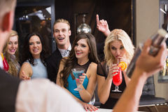 Attractive friends being served cocktails. At the bar Royalty Free Stock Photos