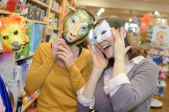 Attractive friends with masks in toy store royalty free stock photography