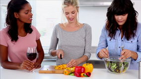 Attractive friends preparing salad in the kitchen stock footage