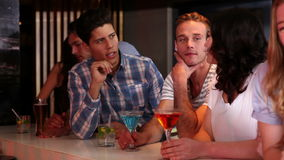 Attractive friends talking and drinking at the bar stock footage