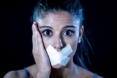 Attractive frightened young woman mouth sealed on adhesive tape stock photography