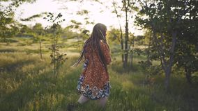 Attractive fun hippie woman with dreadlocks in the woods at sunset having good time outdoors