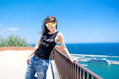 Attractive funky girl on top of docks, seaside view. Royalty Free Stock Images