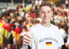 Attractive german fan showing thumb with other fans Royalty Free Stock Photos
