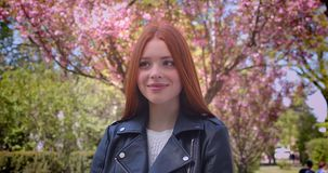 Attractive ginger model in leather jacket posing prettily into camera in pink floral garden. Attractive ginger model in leather jacket posing prettily into stock video footage