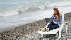 Attractive ginger woman is sitting on sea beach and shopping online. stock video footage