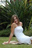 Attractive girl. An attractive sexy smiling young girl in a white wedding dress sitting on the lawn in the garden at home outdoors Stock Images