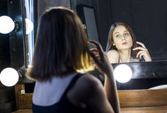 Attractive girl admires itself in mirror Royalty Free Stock Photo