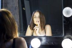 Attractive girl admires itself in mirror Stock Images