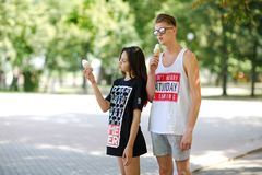 An attractive girl and an appealing fellow eating an ice-cream, dating in a park on a natural blurred background. Stock Image