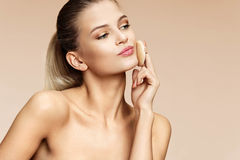 Attractive girl applying powder on her face with cosmetic application. Stock Images
