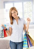 Attractive girl arriving from shopping smiling. Attractive girl arriving from shopping with shopping bags, smiling happily royalty free stock photo