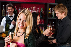 Attractive girl at bar smiling with friends Stock Photos