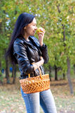 Attractive girl with basket eating an apple Royalty Free Stock Image