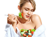 Attractive girl in bathrobe eating fresh salad and smiling. stock photo