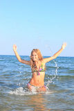 Attractive girl on the beach. Attractive girl in the sea splashing water in Greece Royalty Free Stock Photography