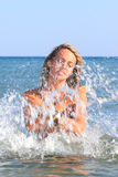 Attractive girl on the beach. Attractive girl in the sea splashing water in Greece Stock Photography