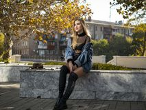 Attractive girl with beautiful flowing hair sits on a bench on a beautiful sunny day