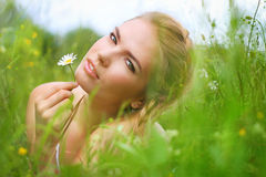 Attractive girl with a beautiful smile dress lies in the field a Stock Photo