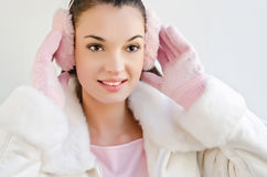Attractive girl with beautiful smile, putting on pink ear muffs. Stock Image