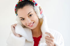 Attractive girl with beautiful smile, wearing ear muffs. Royalty Free Stock Photos