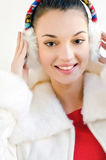 Attractive girl with beautiful smile, wearing ear muffs. Stock Image