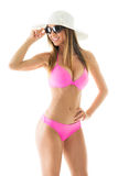 Attractive girl in a bikini. Beautiful young woman smiling and posing in pink bikini with sun hat and sunglasses. Isolated on white background Stock Images