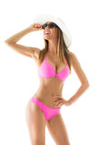 Attractive girl in a bikini. Beautiful young woman smiling and posing in pink bikini with sun hat and sunglasses. Isolated on white background Royalty Free Stock Photo