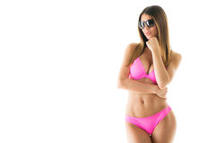 Attractive girl in a bikini. Beautiful young woman smiling and posing in pink bikini with sunglasses. Isolated on white background Royalty Free Stock Photography