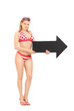 Attractive girl in bikini holding an arrow Royalty Free Stock Photography