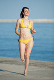 Attractive girl in bikini running along the beach Stock Images