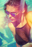 Attractive  girl in bikini and sunglasses in pool Stock Photo