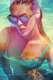 Attractive  girl in bikini and sunglasses in pool Royalty Free Stock Images