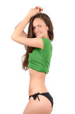 Attractive girl in black bikini and a green top posing from profile showing her curves. Royalty Free Stock Photos