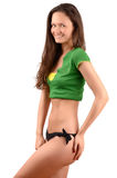 Attractive girl in black bikini and a green top posing from profile showing her curves. Stock Photos