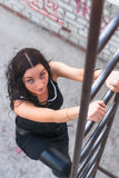Attractive girl in black climbs on ladder Royalty Free Stock Image