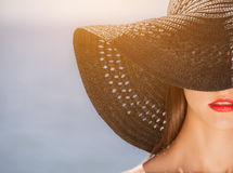 Attractive girl in a black hat worn on the head, on the beach. Royalty Free Stock Images