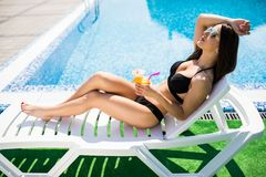 Attractive girl in black swimwear and sun glasses is drinking a cocktail and sunbathing while lying on the chaise longue near the royalty free stock images