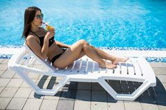 Attractive girl in black swimwear and sun glasses is drinking a cocktail and sunbathing while lying on the chaise longue near the. Attractive girl in swimwear royalty free stock images